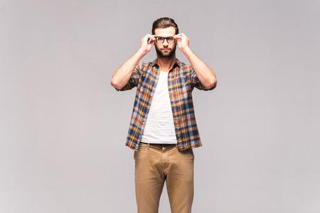Ich kann man deutlich sehen. Studio-Aufnahme von schönen jungen Mann in Freizeitkleidung seine Brille anpassen und Blick in die Kamera Standard-Bild