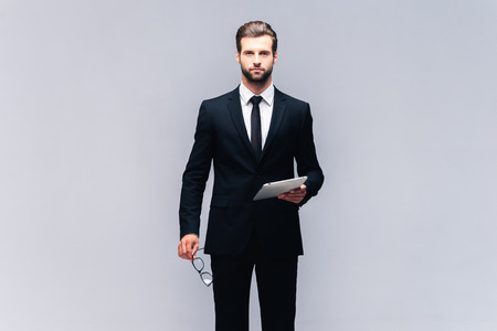 How may I help you? Studio shot of handsome young man in full suit carrying eyeglasses and digital tablet