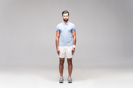 sports clothing: Confident sportsman. Full length of handsome young man in sports clothing looking at camera