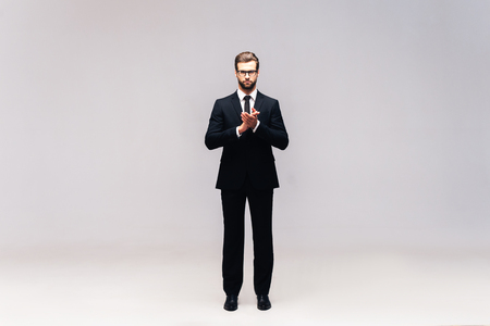 clasped: Confident businessman. Full length studio shot of handsome young man in full suit keeping hands clasped and looking at camera