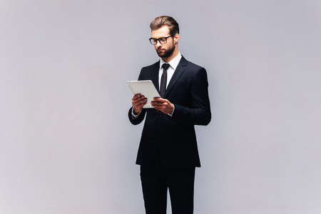 자신감 비즈니스 전문가. 디지털 태블릿에서 작업 전체 소송에서 잘 생긴 젊은 남자의 스튜디오 샷