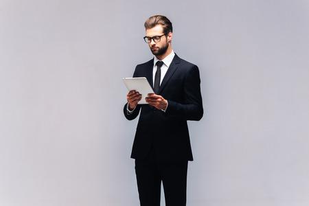 experto de negocios de confianza. Tiro del estudio del hombre joven y guapo en traje completo que trabaja en la tablilla digital