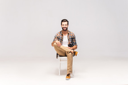Casually handsome. Studio shot of handsome young man sitting on the chair and looking at camera with smile Stock Photo