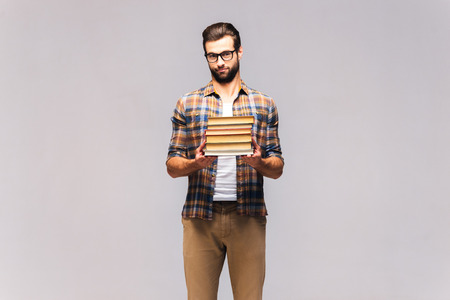 Should I read them all? Studio shot of frustrated young man in eyeglasses and casual wear carrying book stack and looking frustrated
