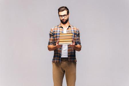 Moet ik ze allemaal lezen? Studio shot van gefrustreerde jonge man in brillen en vrijetijdsbesteding dragen stapel boeken en gefrustreerd kijken