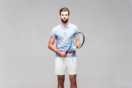 Ready to play. Handsome young man in sports clothing carrying tennis racket and looking at camera Stock Photo