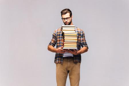 Rat de bibliothèque. Studio, coup seus jeune homme dans des lunettes et des vêtements décontractés transportant livre pile et regarder