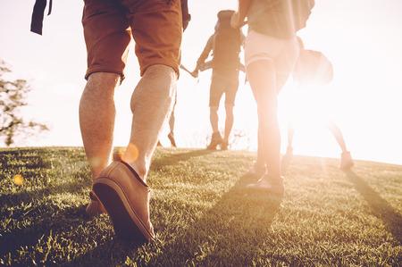 歩き続けて下さい!日の出を背景で緑の草によって移動のバックパックを持つ若い人々 のクローズ アップ背面図