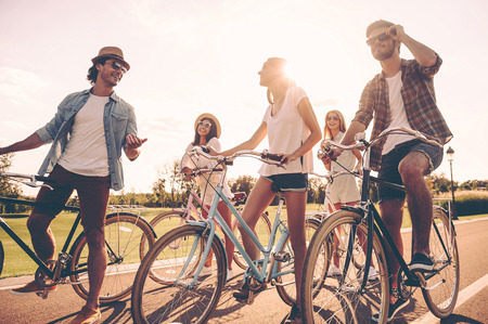 Friends will be friends. Low angle view of cheerful young people talking while standing near their bicycles on the road