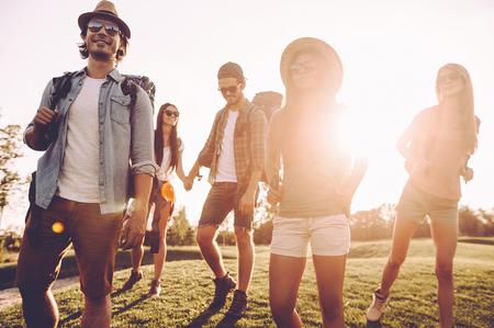 Amigos senderismo. ángulo de visión baja de bellas jóvenes con mochilas caminando juntos y mirando feliz