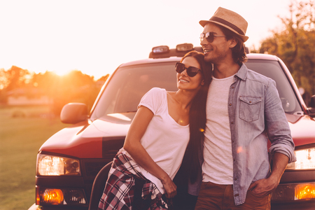 leaning on the truck: Thinking about new place to go. Beautiful young smiling couple looking thoughtful while bonding to each other and leaning at their pick-up truck Stock Photo
