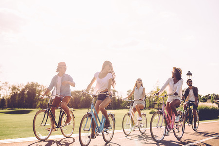 road ahead: Best friends and road ahead. Group of young people riding bicycles along a road and looking happy Stock Photo