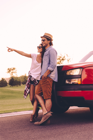 leaning on the truck: Look at that! Full length of beautiful young couple bonding to each other and leaning at their pick-up truck while woman pointing away and smiling