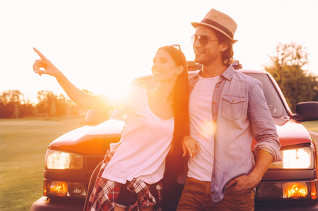 leaning on the truck: Just look over there! Beautiful young couple bonding to each other and leaning at their pick-up truck while woman pointing away and smiling Stock Photo