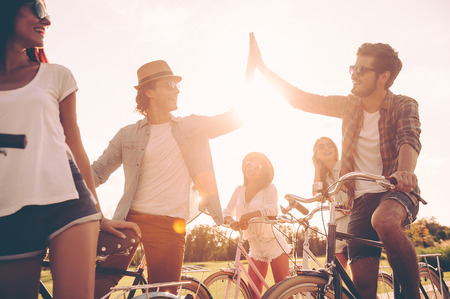 high angle: High five! Low angle view of cheerful young people standing near their bicycles on the road while two men giving high five Stock Photo