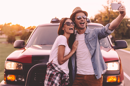 leaning on the truck: Capturing fun. Beautiful young couple bonding to each other and leaning at their pick-up truck while making selfie Stock Photo