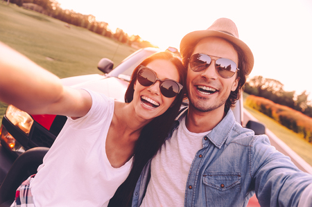 leaning on the truck: We love selfie! Beautiful young couple bonding to each other and leaning at their pick-up truck while making selfie Stock Photo