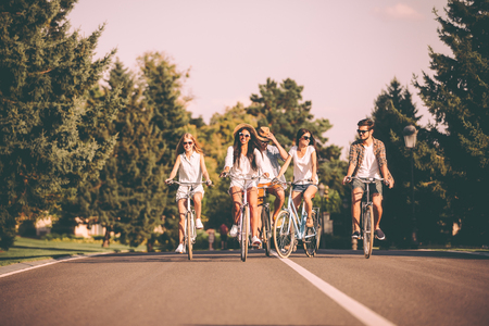 people travelling: Cycling with fun. Group of young people riding bicycles along a road and looking happy