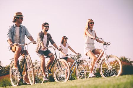 가장 친한 친구와 자전거 타기. 자전거를 타고 행복하게 보이는 젊은 사람들의 그룹