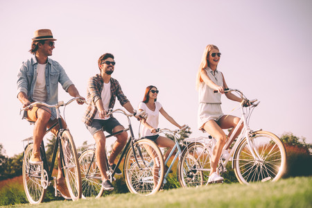 Cycling with best friends. Group of young people riding bicycles and looking happy