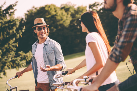 Carefree talk with friends. Handsome young man in fedora standing near his bicycle while talking to his friends outdoors