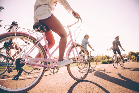 Carefree ride. Low angle view of young cheerful people riding bicycles along a road together Stock Photo