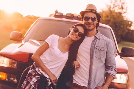leaning on the truck: Ready to road trip. Beautiful young smiling couple bonding to each other and leaning at their pick-up truck Stock Photo