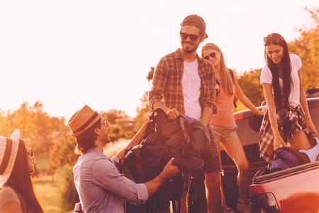 mochila de viaje: Cargando mochilas en un camión. hermosa gente joven que cargan sus mochilas al camión de recogida y mirando contento con la puesta del sol en los fondos Foto de archivo