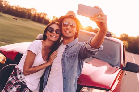 leaning on the truck: Selfie time! Beautiful young couple bonding to each other and leaning at their pick-up truck while making selfie