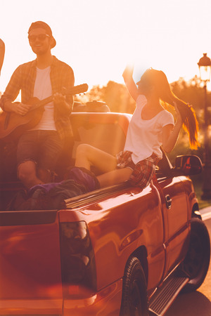 pickup truck: Enjoying perfect road trip. Beautiful young couple enjoying road trip while sitting in pick-up truck