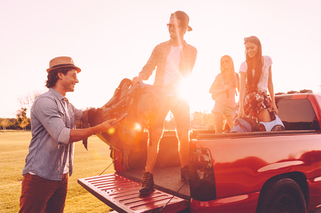 travel backgrounds: Preparation before travel. Beautiful young people loading their backpacks to pick-up truck and looking happy with sunset in the backgrounds Stock Photo