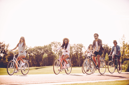 Cycling with fun. Group of young people riding bicycles along a road and looking happy