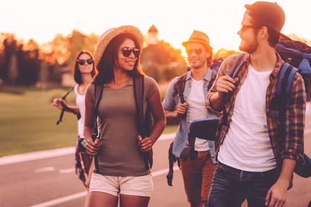 jovenes felices: Tener libertad para ir a cualquier parte. Grupo de jóvenes con mochilas caminando juntos por la carretera y que parece feliz