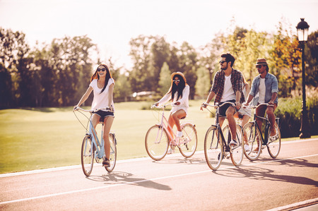 young group: Enjoying great time together. Group of young people riding bicycles along a road and looking happy