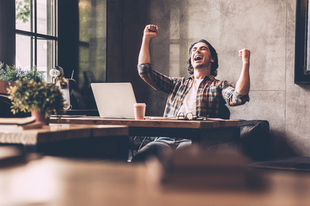 winner man: Everyday winner. Cheerful young man in casual wear keeping arms raised and looking happy while sitting at the desk in office