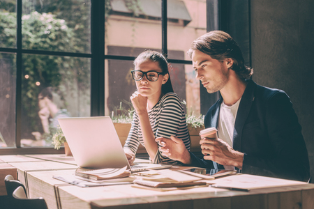 woman work: Concentrated at work. Confident young man and woman looking at laptop while both sitting at the wooden desk in creative office or cafe