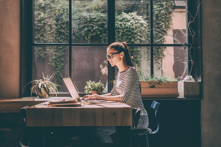Concentrated at work. Confident young woman in smart casual wear working on laptop while sitting near window in creative office or cafe Stockfoto