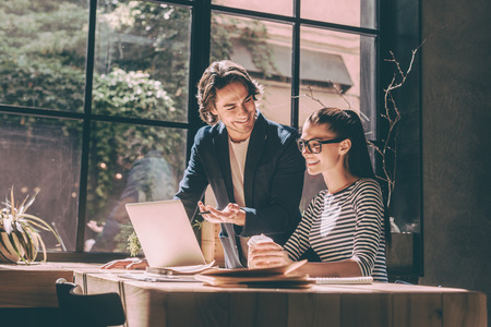 confident woman: Working with pleasure. Confident young man and woman looking at laptop and smiling while sitting at the wooden desk in creative office or cafe