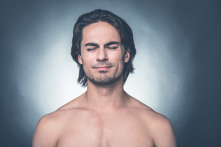 expressing negativity: Feeling not good. Portrait of young shirtless man keeping eyes closed and expressing negativity while standing against grey background