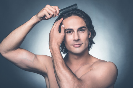 metrosexual: Everything should be perfect. Portrait of young shirtless man combing his hair with hairbrush and looking at camera while standing against grey background