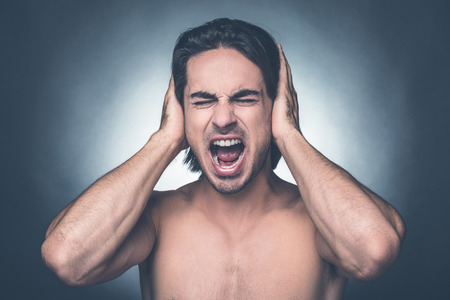 only adult: Too loud sound. Portrait of frustrated young shirtless man keeping eyes closed and covering ears with hands while standing against grey background