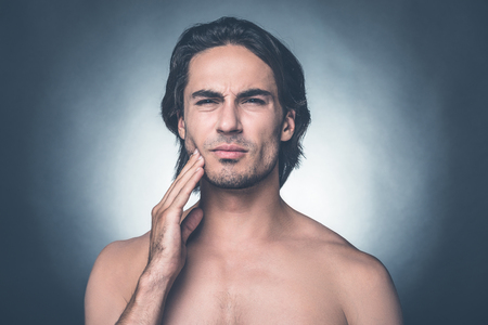 expressing negativity: Feeling that awful toothache. Portrait of young shirtless man expressing negativity while touching cheek and standing against grey background