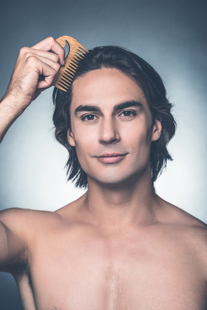 Combing to perfection. Portrait of young shirtless man combing his hair with hairbrush and looking at camera while standing against grey background