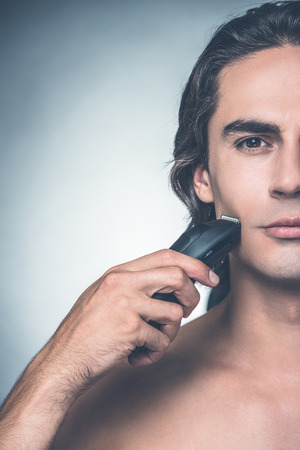 half full: Shaving with electric razor. Half full of young shirtless man shaving with electric razor and looking at camera while standing against grey background