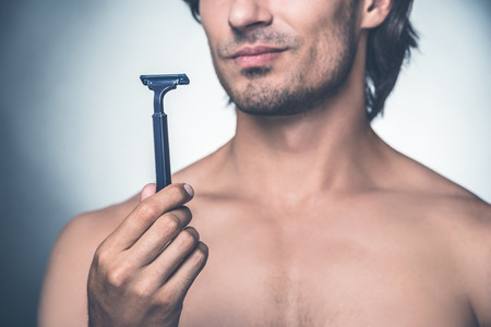 expressing negativity: Time for new razor. Close-up young shirtless man holding razor and expressing negativity while standing against grey background Stock Photo