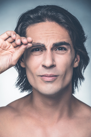 tweezing: Tweezing eyebrows. Portrait of young shirtless man tweezing eyebrows and expressing negativity while standing against grey background Stock Photo