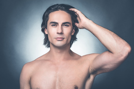 metrosexual: Looking just perfect. Portrait of young shirtless man looking at camera and adjusting his hairstyle while standing against grey background