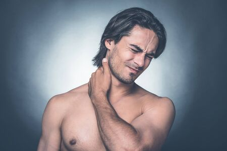 expressing negativity: Feeling pain in neck. Portrait of young shirtless man keeping eyes closed and expressing negativity while touching his neck and standing against grey background Stock Photo