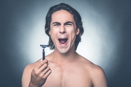 expressing negativity: Bad razor. Young shirtless man holding razor and expressing negativity while standing against grey background