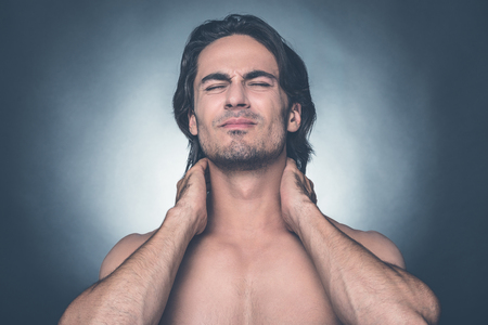 expressing negativity: Feeling that awful pain. Portrait of young shirtless man keeping eyes closed and expressing negativity while touching his neck and standing against grey background